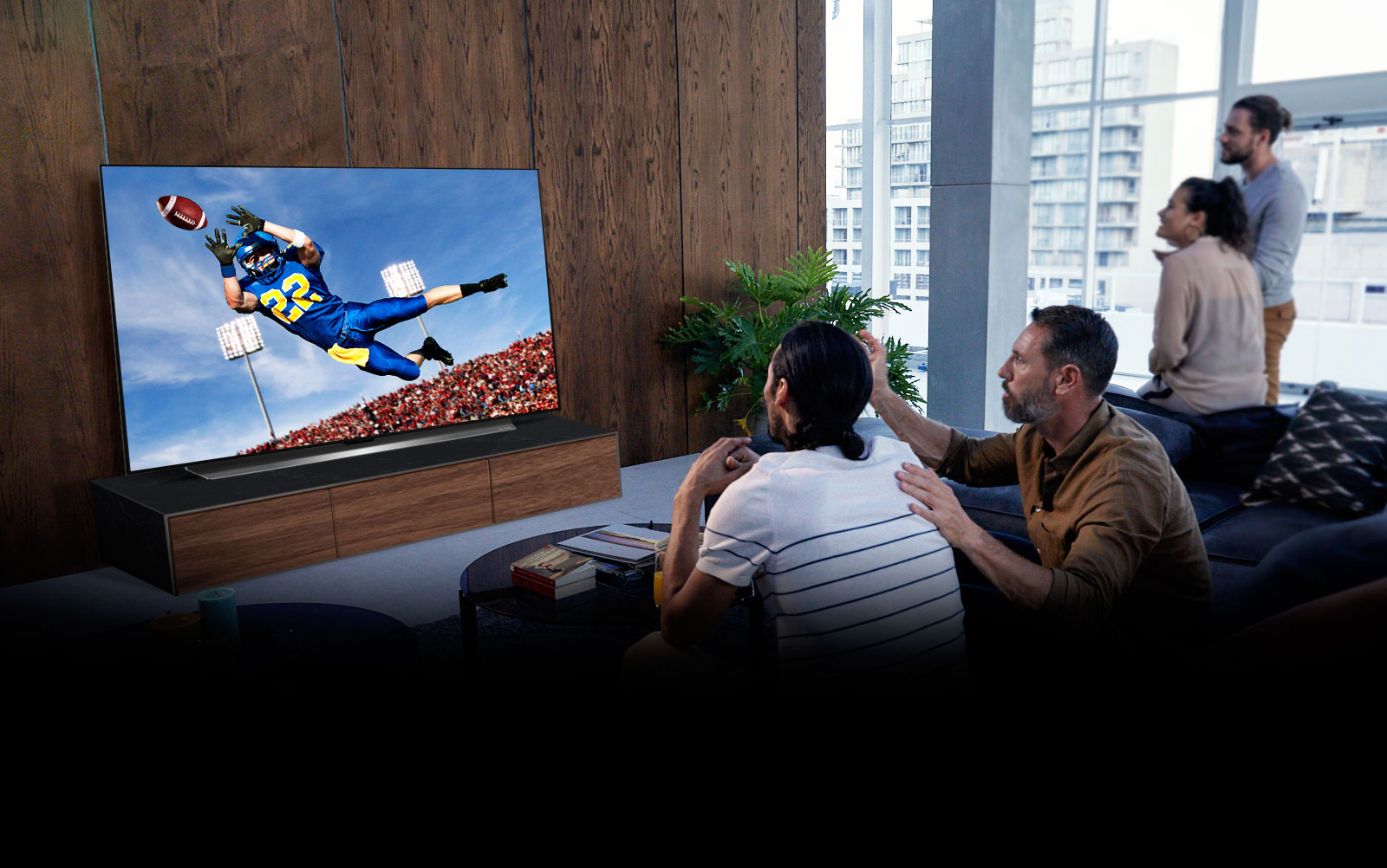People watching a American football game on TV in the living room
