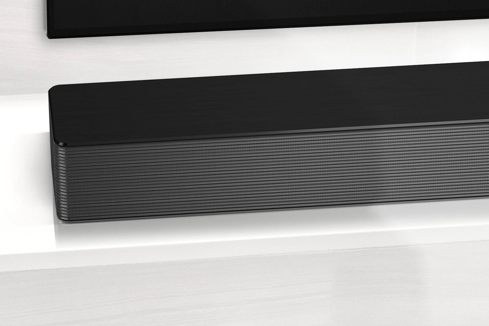 Close-up of LG Soundbar left corner. Bottom left side of TV is also visible.