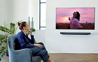 a woman watching TV on the single couch