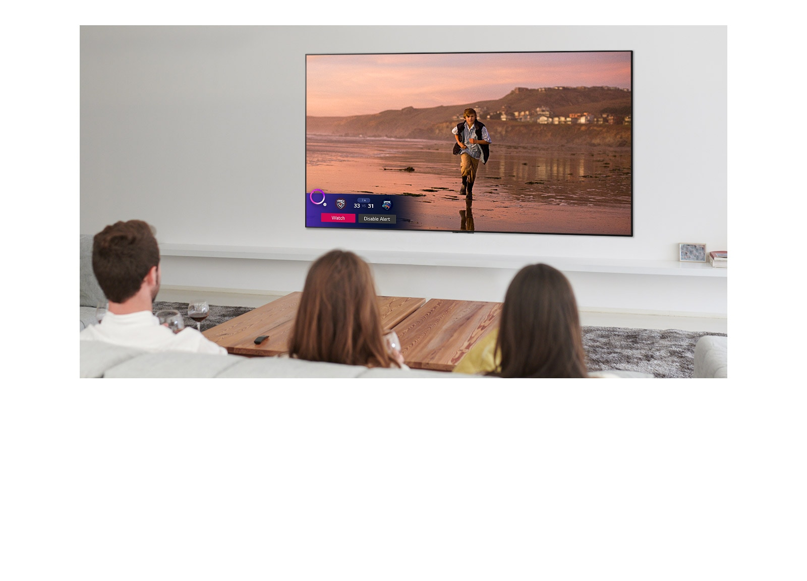 Three people watching TV screen showing a scene from a fantasy movie with a Sports Alert