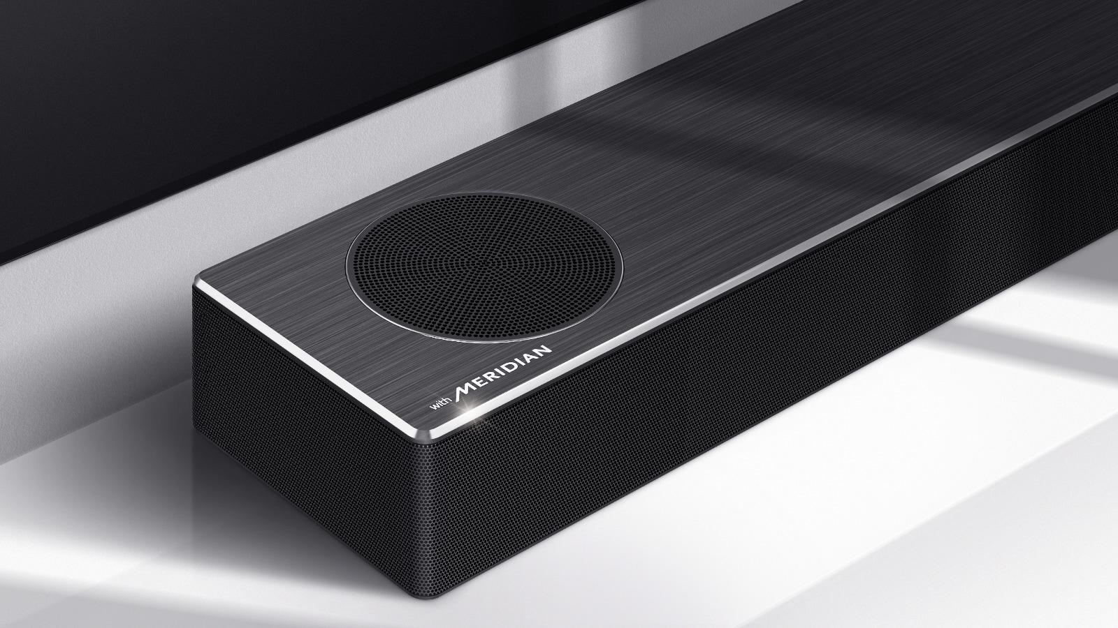 Close-up of LG Soundbar left side with Meridian logo shown on bottom left corner on a product. Bottom left side of TV is also visible.