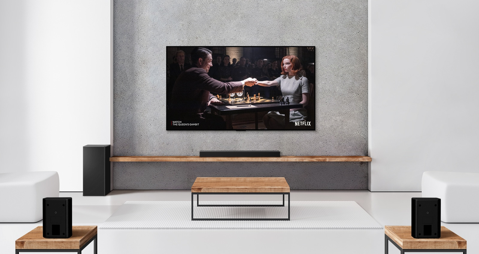 A set of 2 rear speakers, subwoofer, and a soundbar, and TV are in a white living room. A woman and a man are playing chess on TV screen.