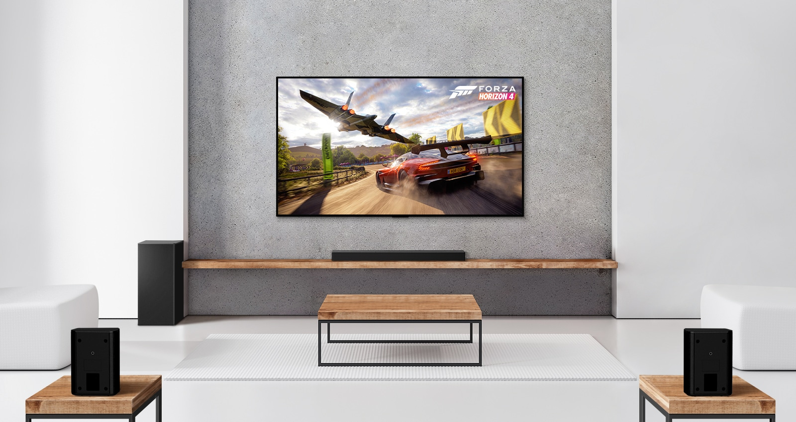 A set of 2 rear speakers, subwoofer, and a soundbar, and TV are in a white living room. A driving car and a spaceship are on TV screen.