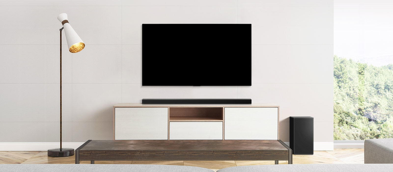 A TV, soundbar, and subwoofer placed in a plain living room.