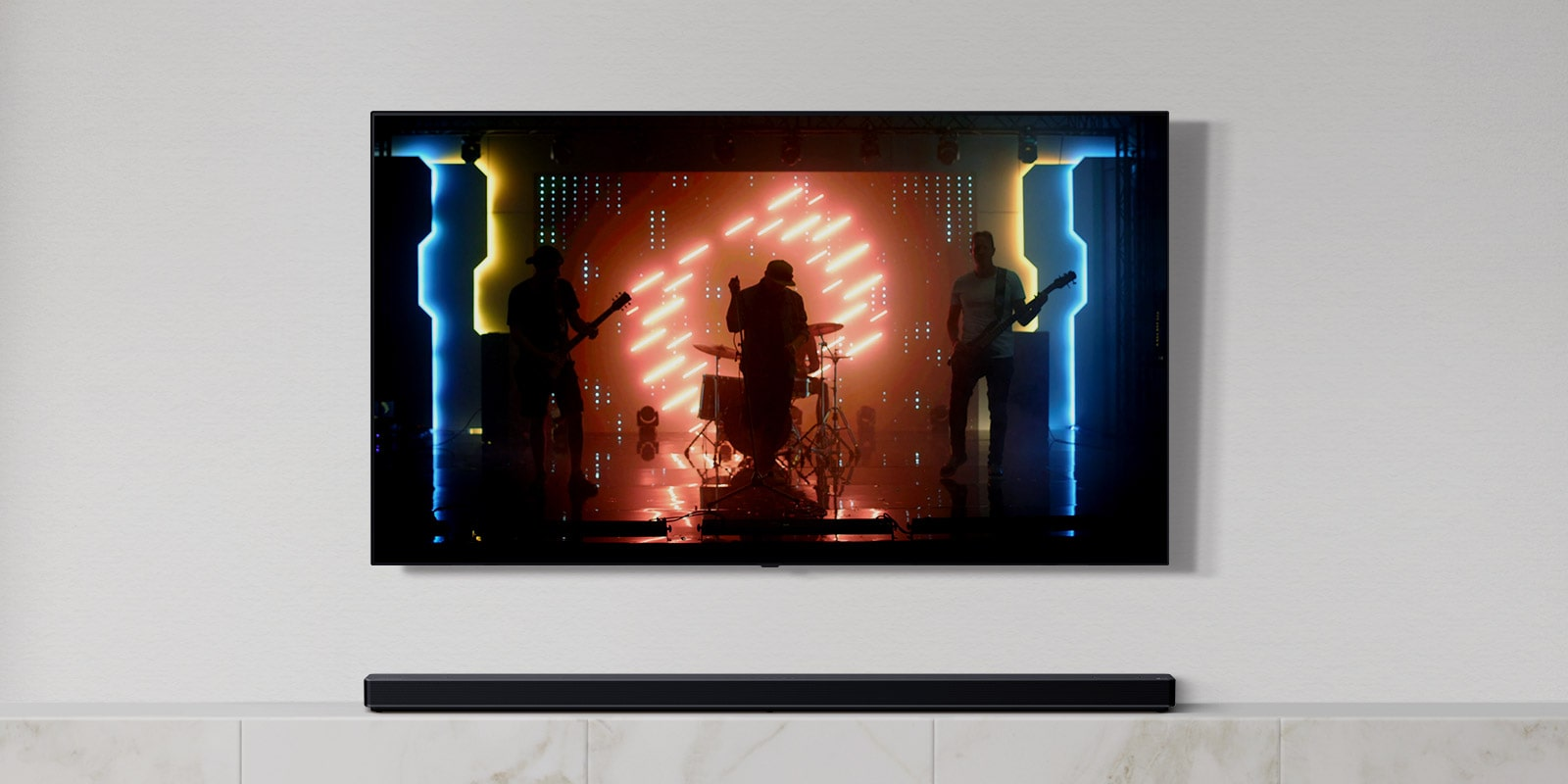 There is a TV and a soundbar in white living room. A group of band playing instruments and singing song on a TV screen. (play the video)
