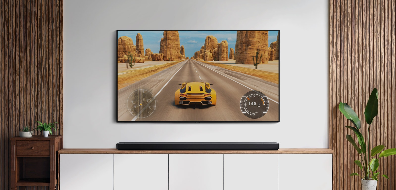 There is TV and a soundbar in a living room. A car racing game is on a TV screen. (play the video)