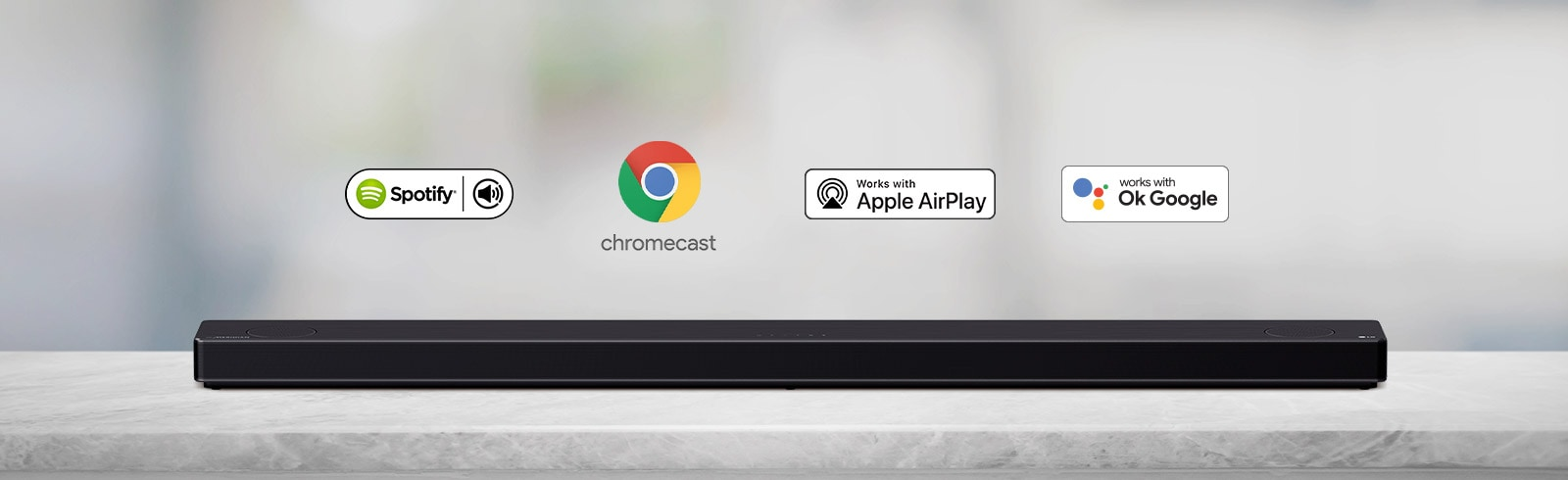 There is a soundbar placed on a gray shelf and there are AI platform logos, in order of Spotify, Alexa, Chromecast, Apple Airplay, and OK Google from left to right.