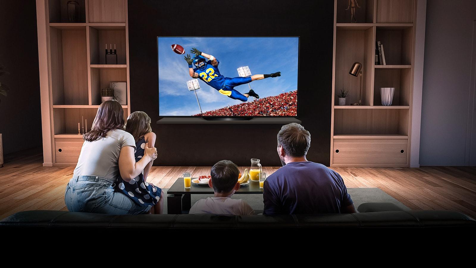 Ľudia v obývacej izbe sledujú na televízore zápas Tottenhamu