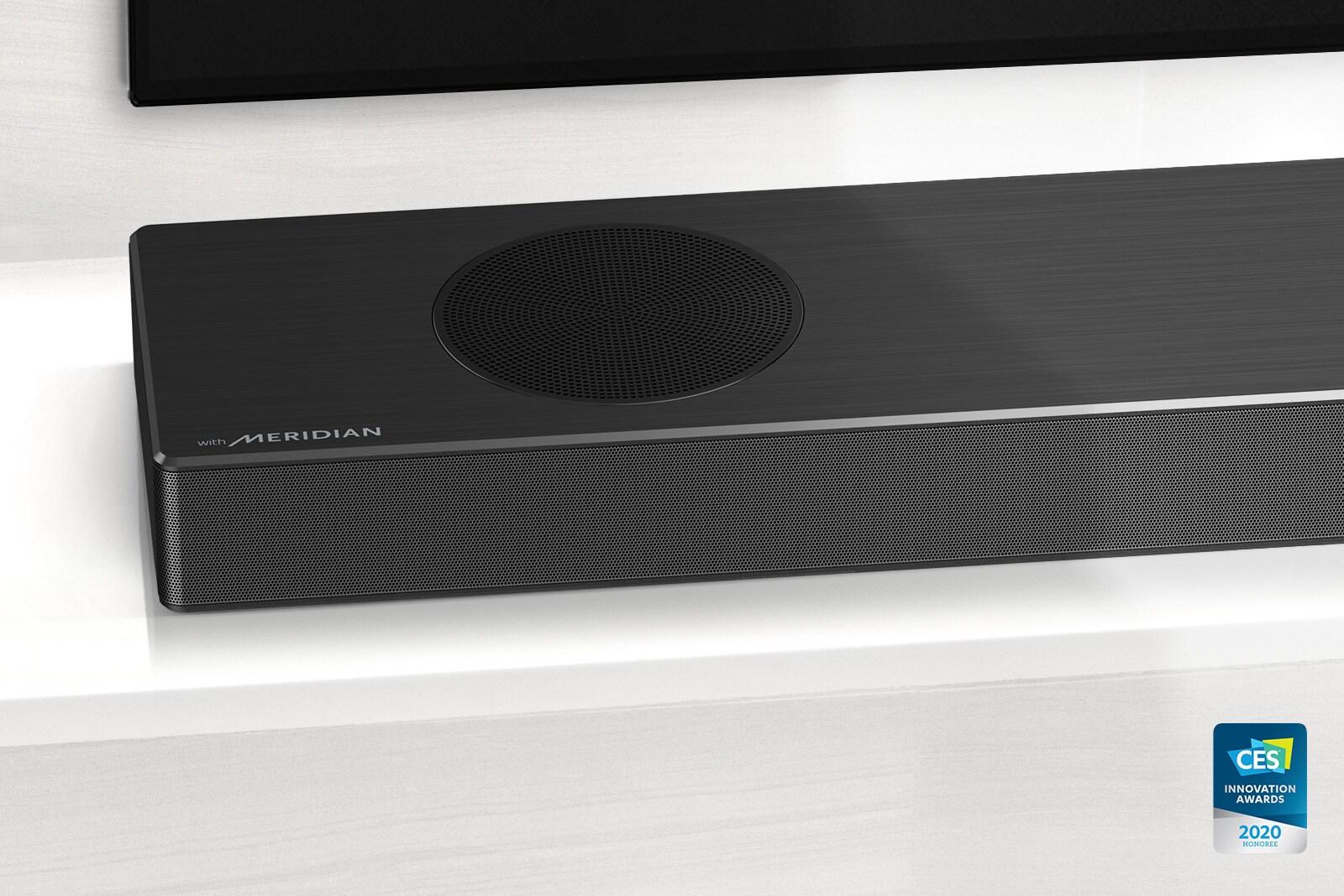 Close-up ของ LG Soundbar ด้านซ้ายพร้อมโลโก้ Meridian ที่มุมล่างซ้าย ด้านล่างซ้ายของทีวียังมองเห็นได้