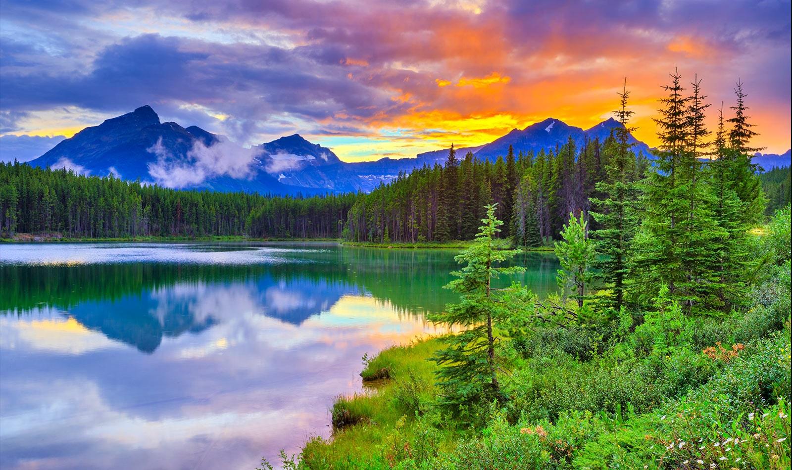 บัตรนี้อธิบายคุณภาพรูปภาพ เป็นรูปภาพดวงอาทิตย์ตกดินที่มีสีสันหลากหลายในทะเลสาบที่แวดล้อมไปด้วยป่า