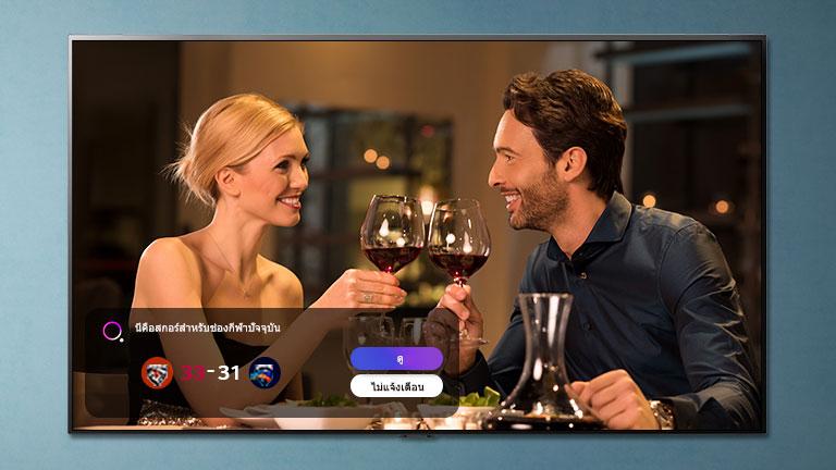 ผู้ชายและผู้หญิงกำลังชนแก้วกันบนจอทีวี ขณะที่ sports alerts กำลังแจ้งเตือน