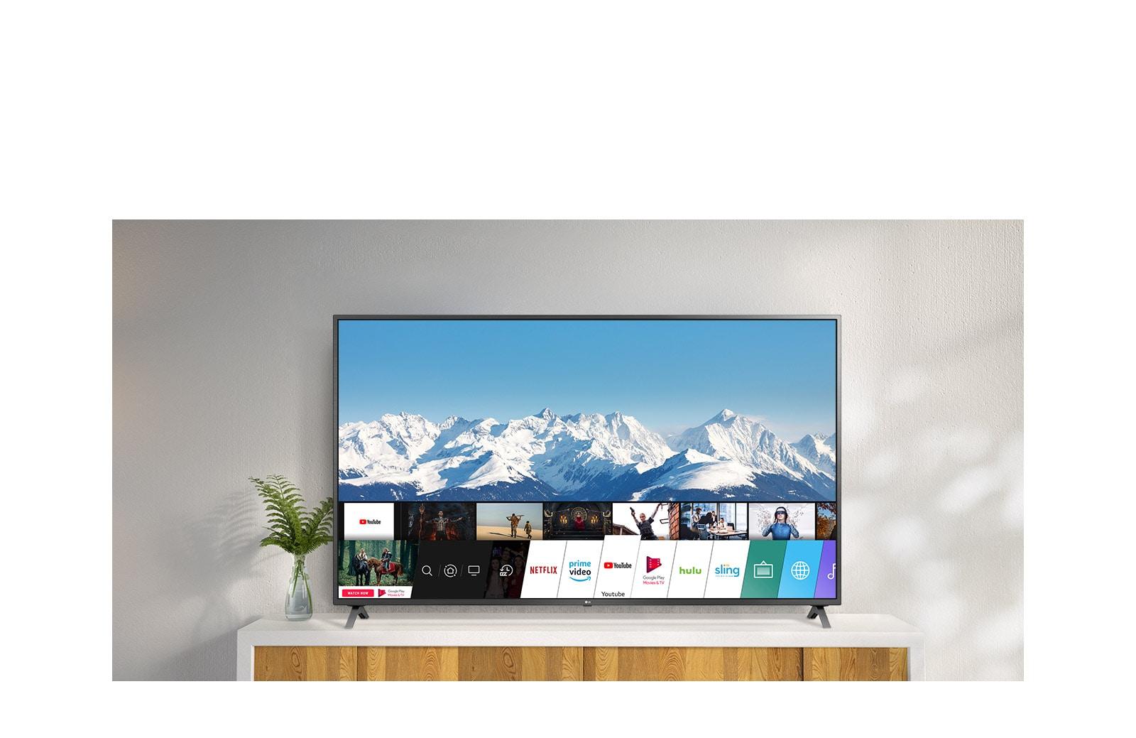 ทีวีกำลังตั้งอยู่บนขาตั้งสีขาวและผนังสีขาว หน้าจอทีวีแสดงหน้าจาหลักที่มี webOS