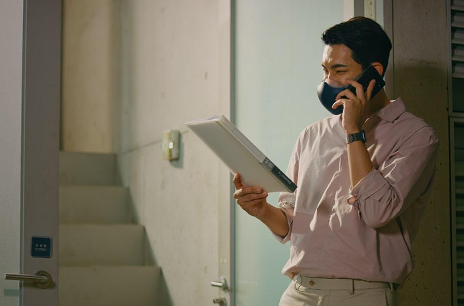 ชายเอเชียคนหนึ่งกำลังถือเอกสารและพูดโทรศัพท์อยู่ โดยมีหน้ากากฟอกอากาศ  LG PuriCare™ สีดำเปิดอยู่