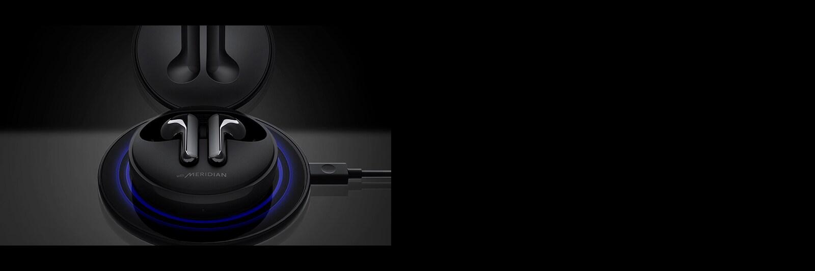 ภาพ LG TONE Free FN6 สีดำที่เปิดอยู่ กำลังชาร์จอยู่บนแผ่นชาร์จไร้สายสีดำ พร้อมด้วยแสงไฟสีฟ้า