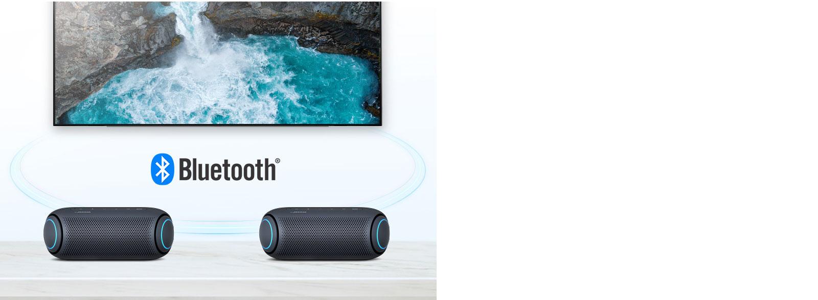 LG XBOOM Go สองเครื่องที่สีแสงสีน้ำเงินบนโต๊ะวางอยู่ด้านหน้าทีวีที่กำลังแสดงภาพน้ำตก