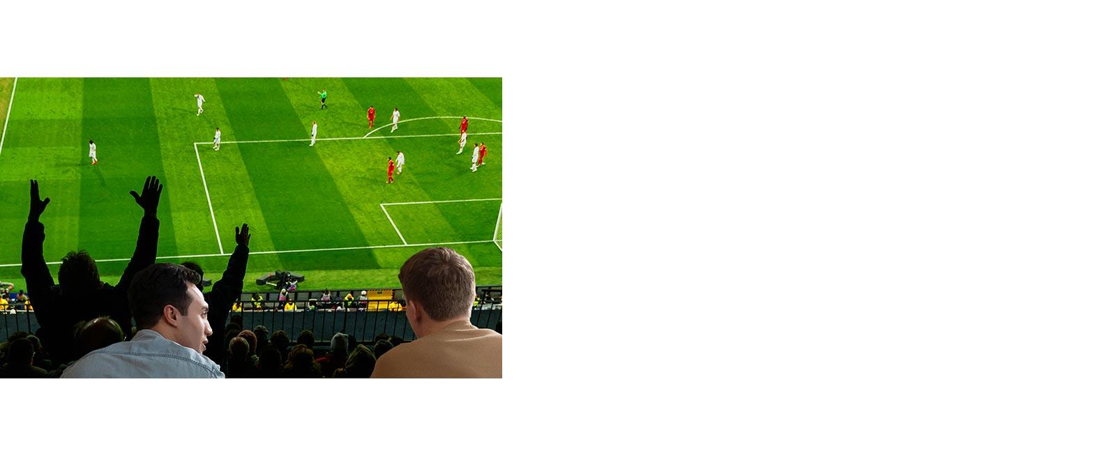 Oturma odasında ultra geniş ekranlı televizyonda maç izleyen insanlar