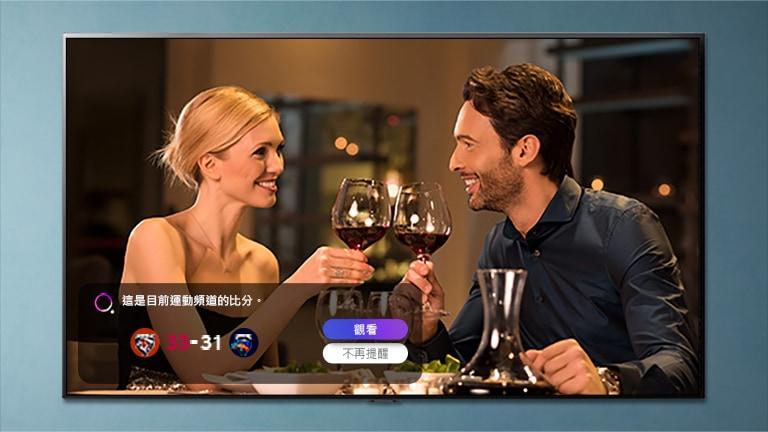 在賽事提醒響起時,一個男人和一個女人在電視螢幕上碰杯