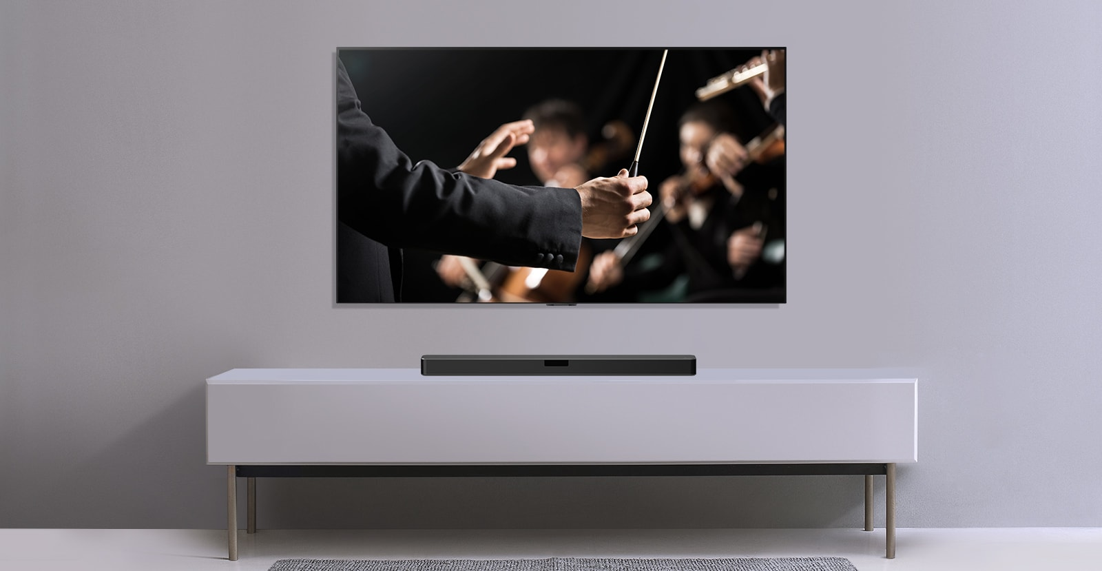 Зображення телевізора на сірій стіні та під ним саундбара LG на сірому низькому комоді. На екрані телевізора— диригент оркестру під час концерту.