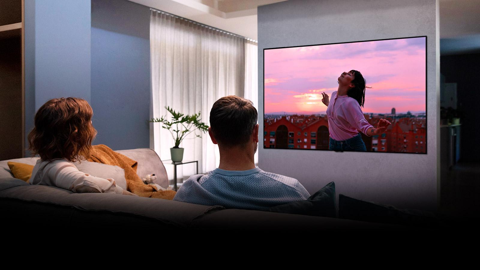 Пара сидить на дивані у вітальні, дивлячись романтичний фільм по телевізору