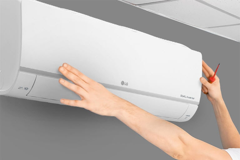 The side view of the air conditioner can be seen on the wall. Two hands are reaching up, one holding a tool, showing the ease of installation.