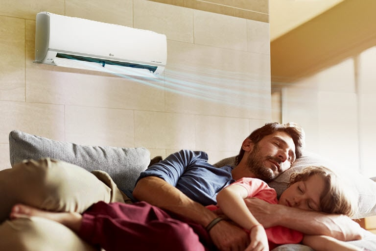 A father and daughter sleep on a couch beneath an air conditioner that is blowing air out over them.