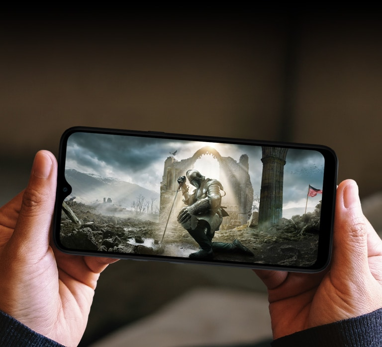 Woman holding a smartphone with both hands and watching a medieval movie