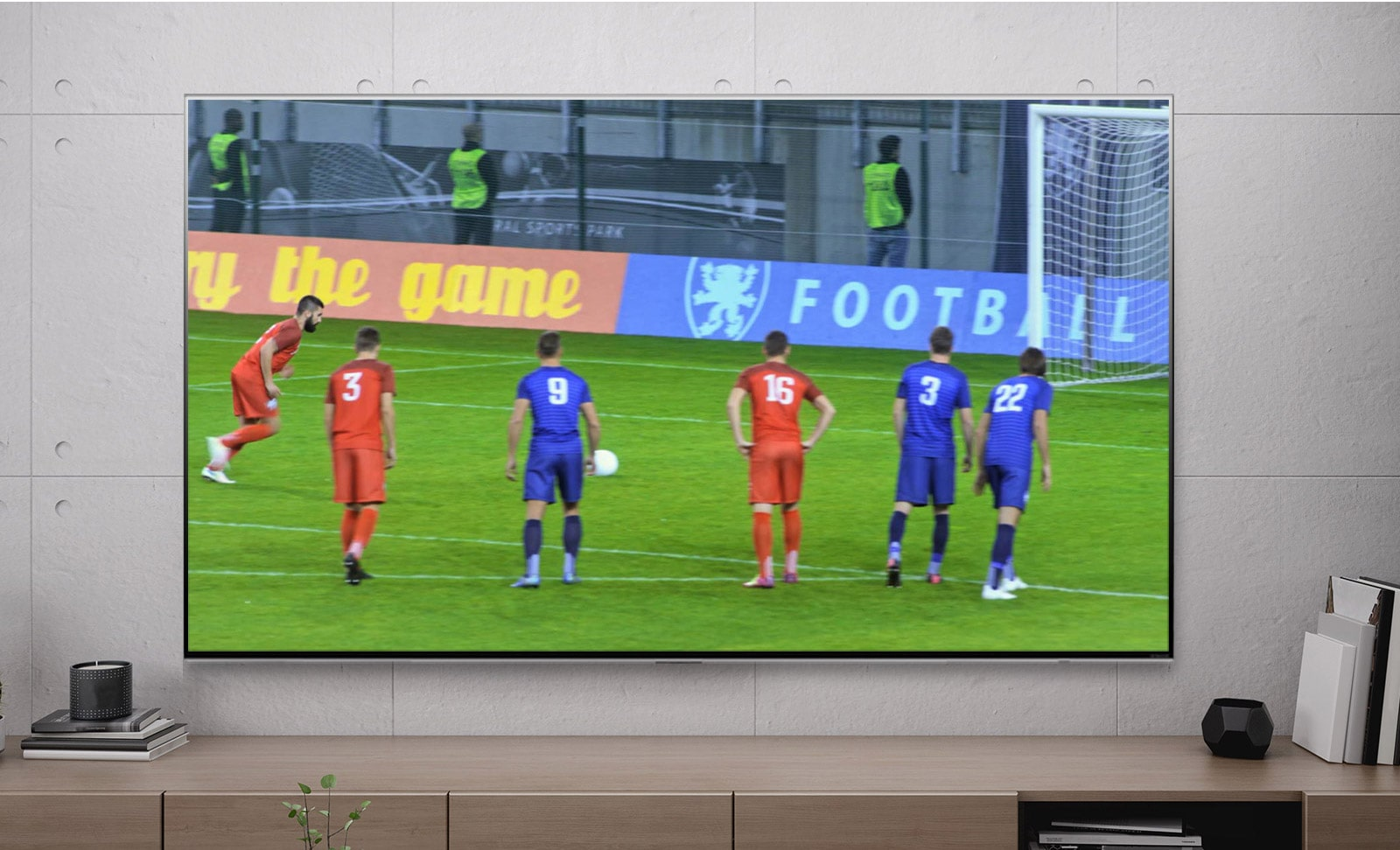 A TV screen showing a football player scoring a penalty (play the video).