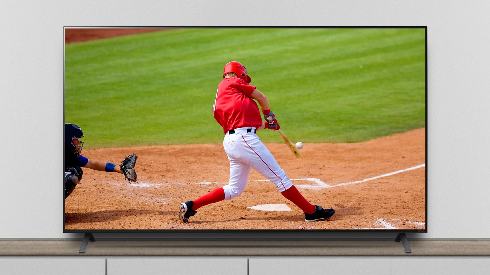 The TV is on the stand, and the screen shows a baseball match.