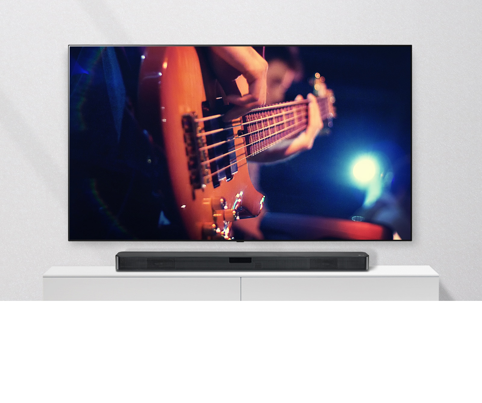The TV is attached to the wall, and the sound bar is on a white shelf. TV showing a man plays guitar.