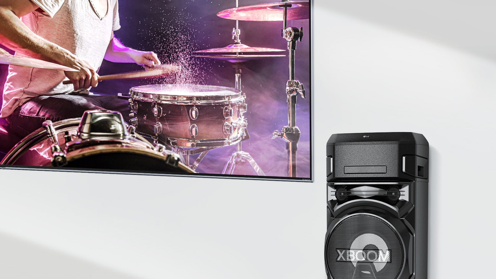 A TV is on a wall with an LG XBOOM to the right of it.