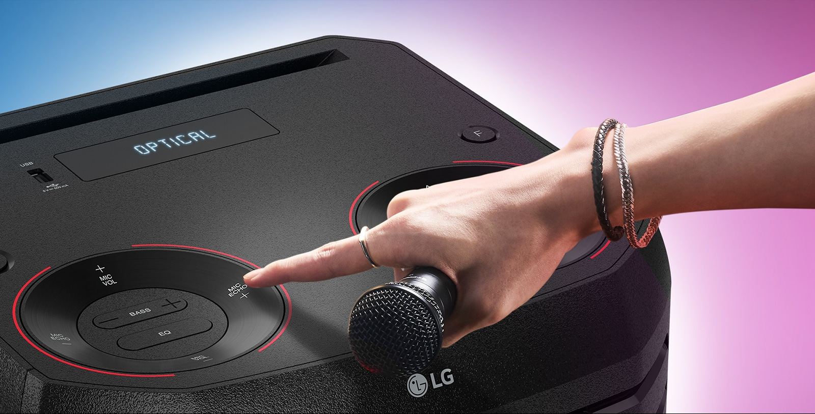 A hand holding a microphone tries to press the Mic echo button on the top of LG XBOOM.
