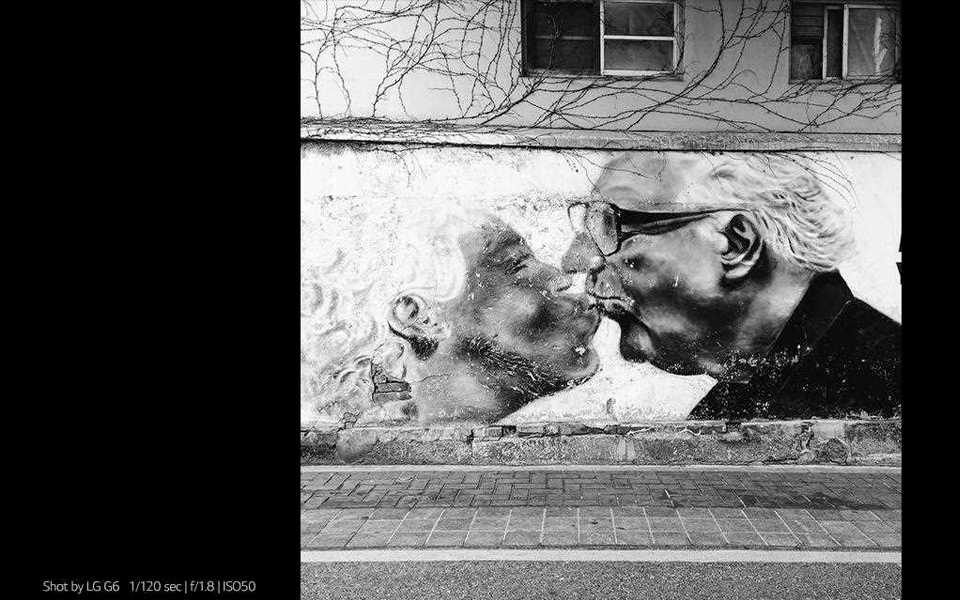 A photography of graffiti of a kissing couple on the street shot by lg g6