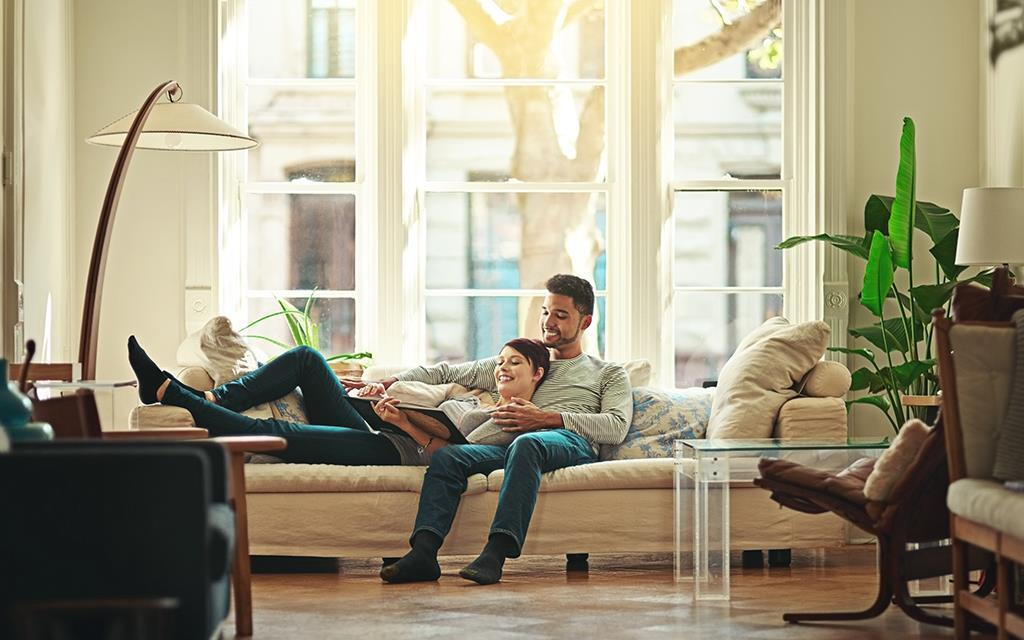 A couple is in a family living room reading a book on the sofa