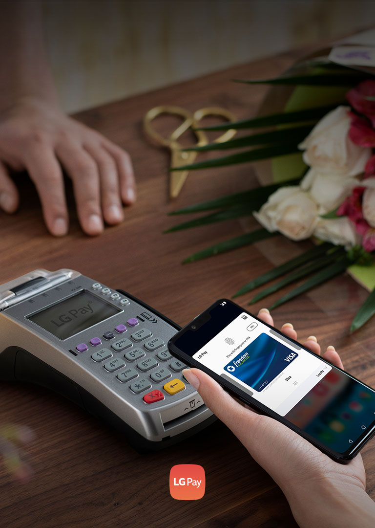 person holding the G8 to a card scanner to pay