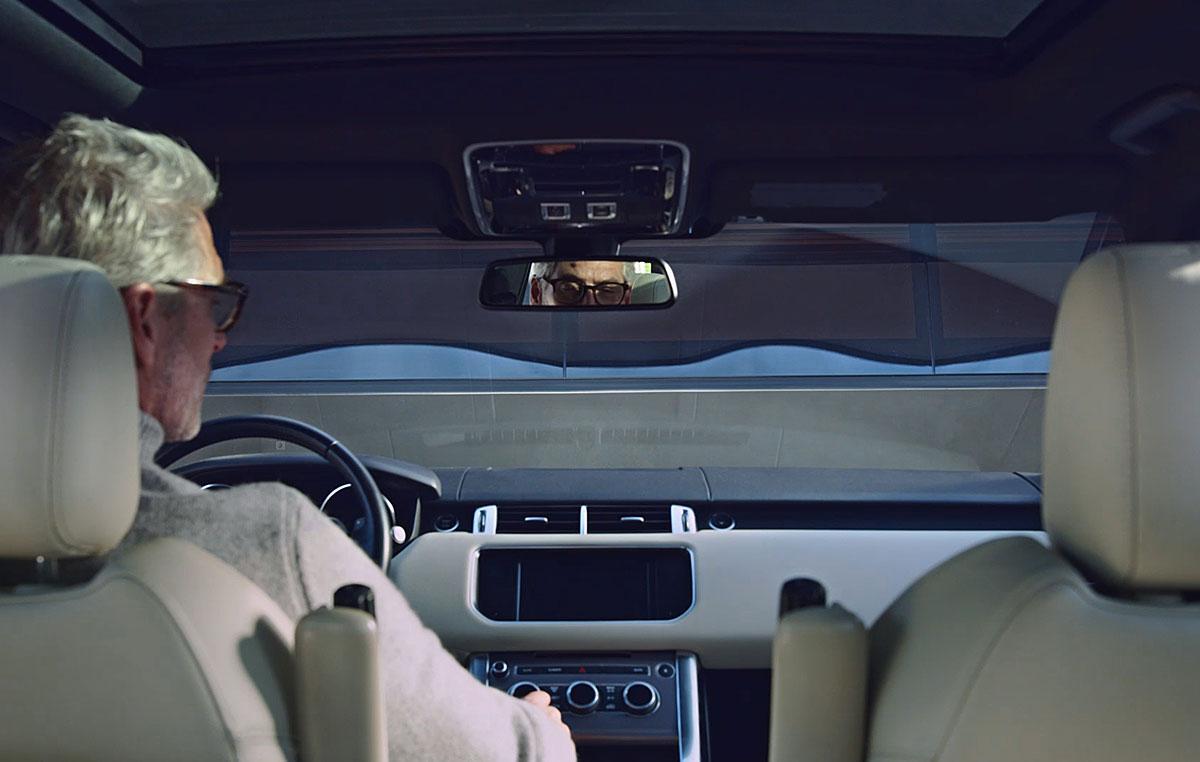 Человек в водительском кресле меняет станции на автомобильном радио