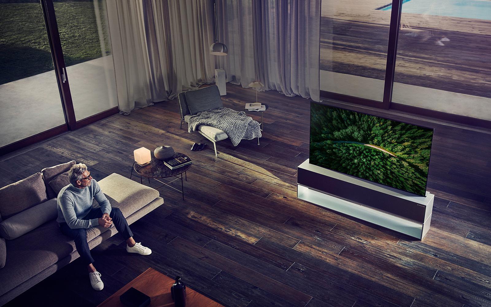 Человек смотрит телевизор в роскошной гостиной.