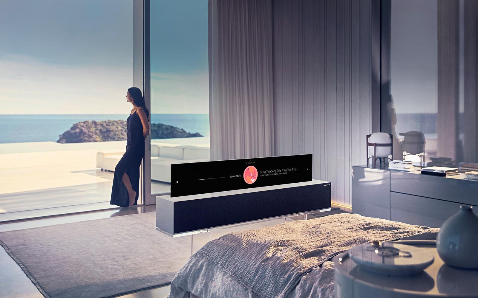 Женщина стоит у окна, наблюдая за видом на пляж из своей спальни.