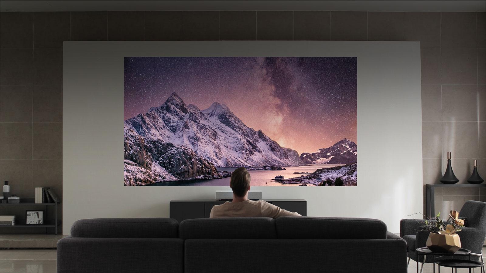 人觀看在白色牆壁上的山風景投射。