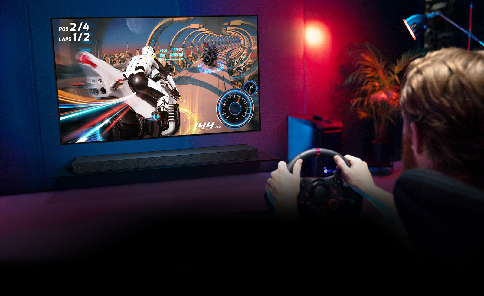 Man sitting on a racer gaming chair, holding a racing wheel while playing a racing game on a TV screen