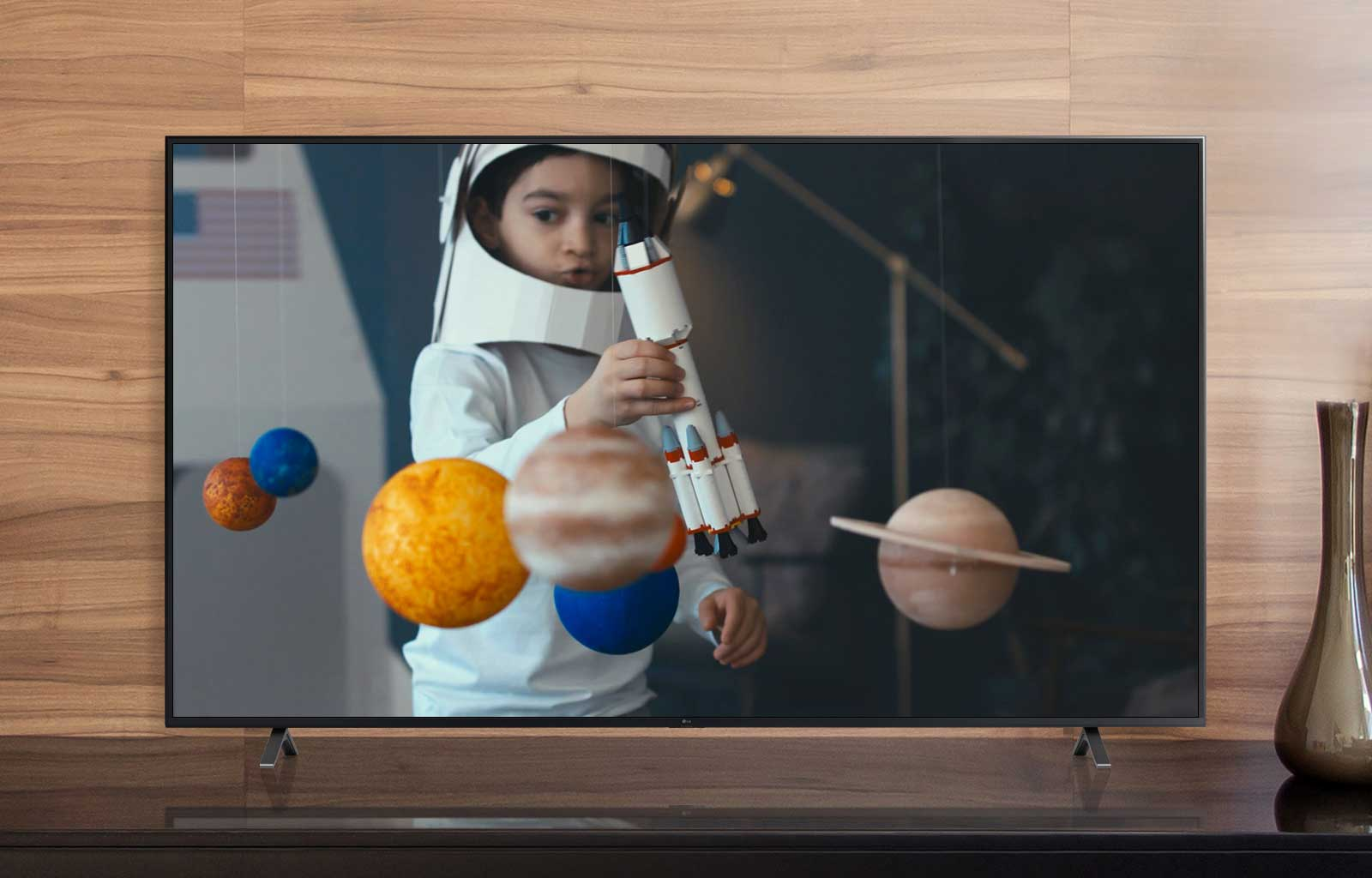 A TV screenplaying a video of a boy in an astronaut suit he made playing with a spaceship in his room decorated with miniatures of planets (play the video)