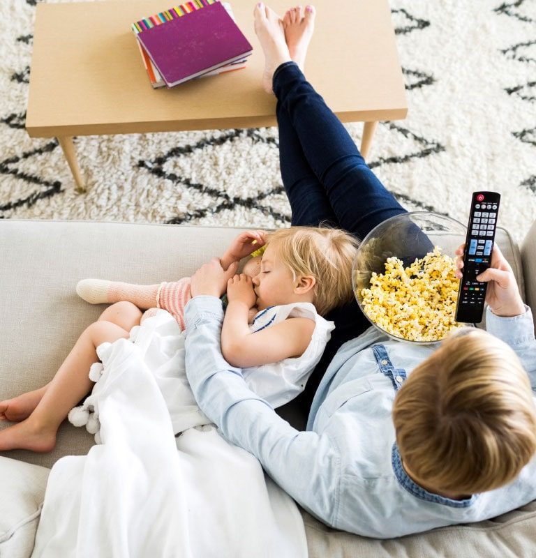 Adult and child sitting on couch