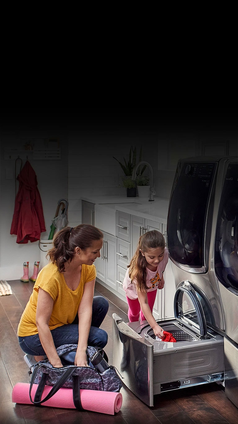 Woman and child placing clothes inside the pedestal washer