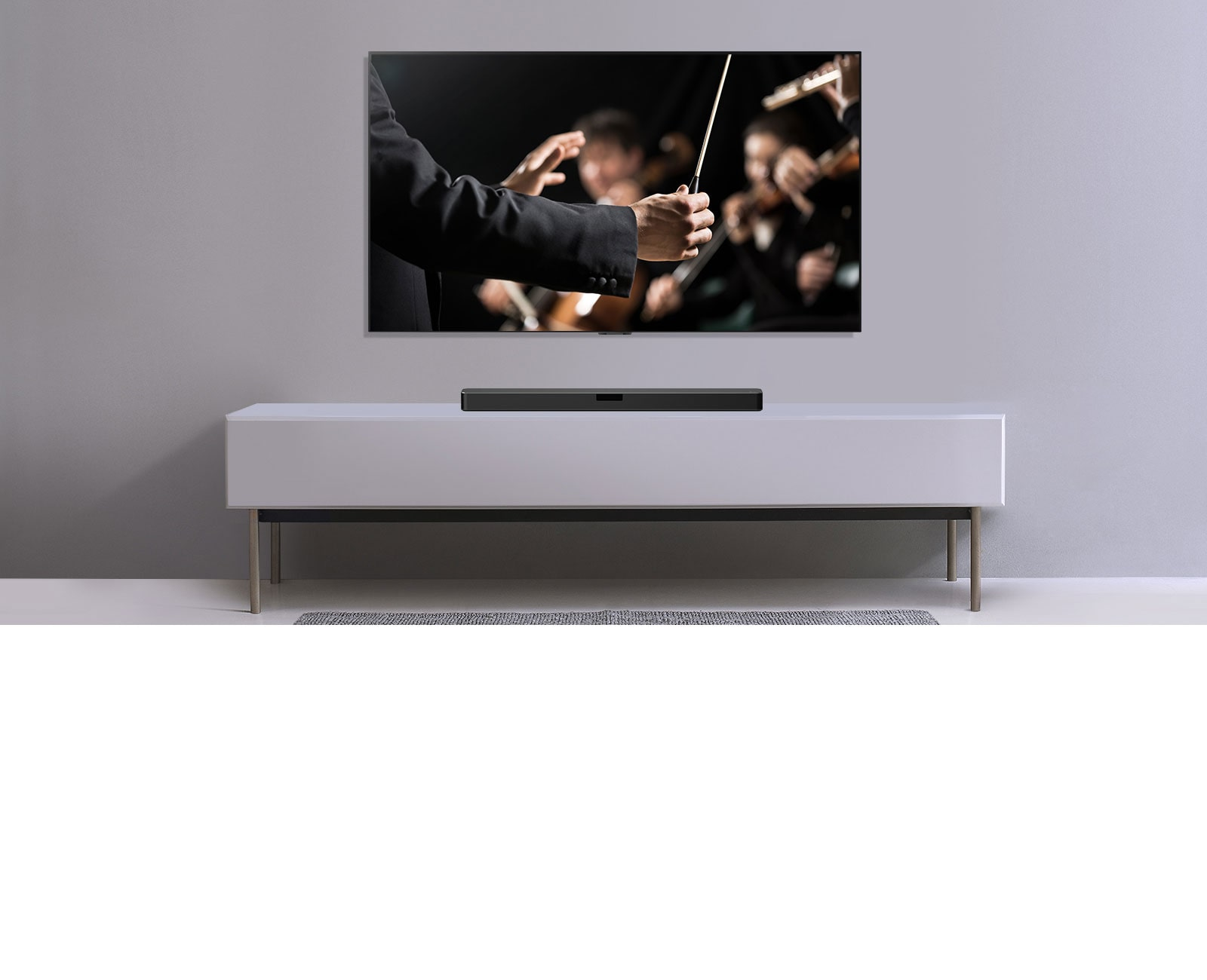 A TV is shown on a gray wall and LG Soundbar below it on a gray shelf. TV shows a conductor conducting an orchestra.