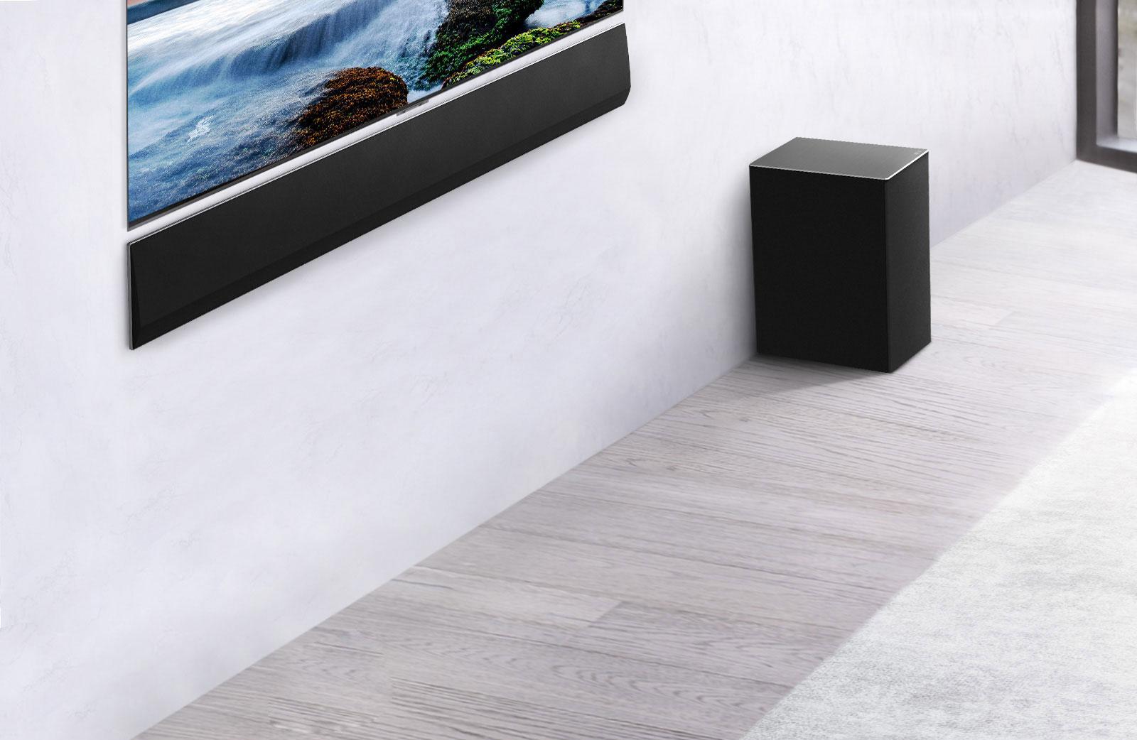 Televizor in LG Soundbar sta nameščena na steno z nizkotoncem spodaj in desno.  Televizija prikazuje sončni zahod na morju.