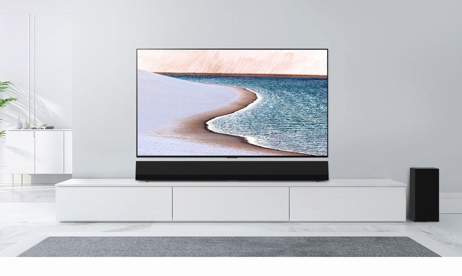 Na svetlo sivi steni je nameščen televizor.  LG Soundbar je pod njim na beli omari.  Televizor prikazuje plažo.