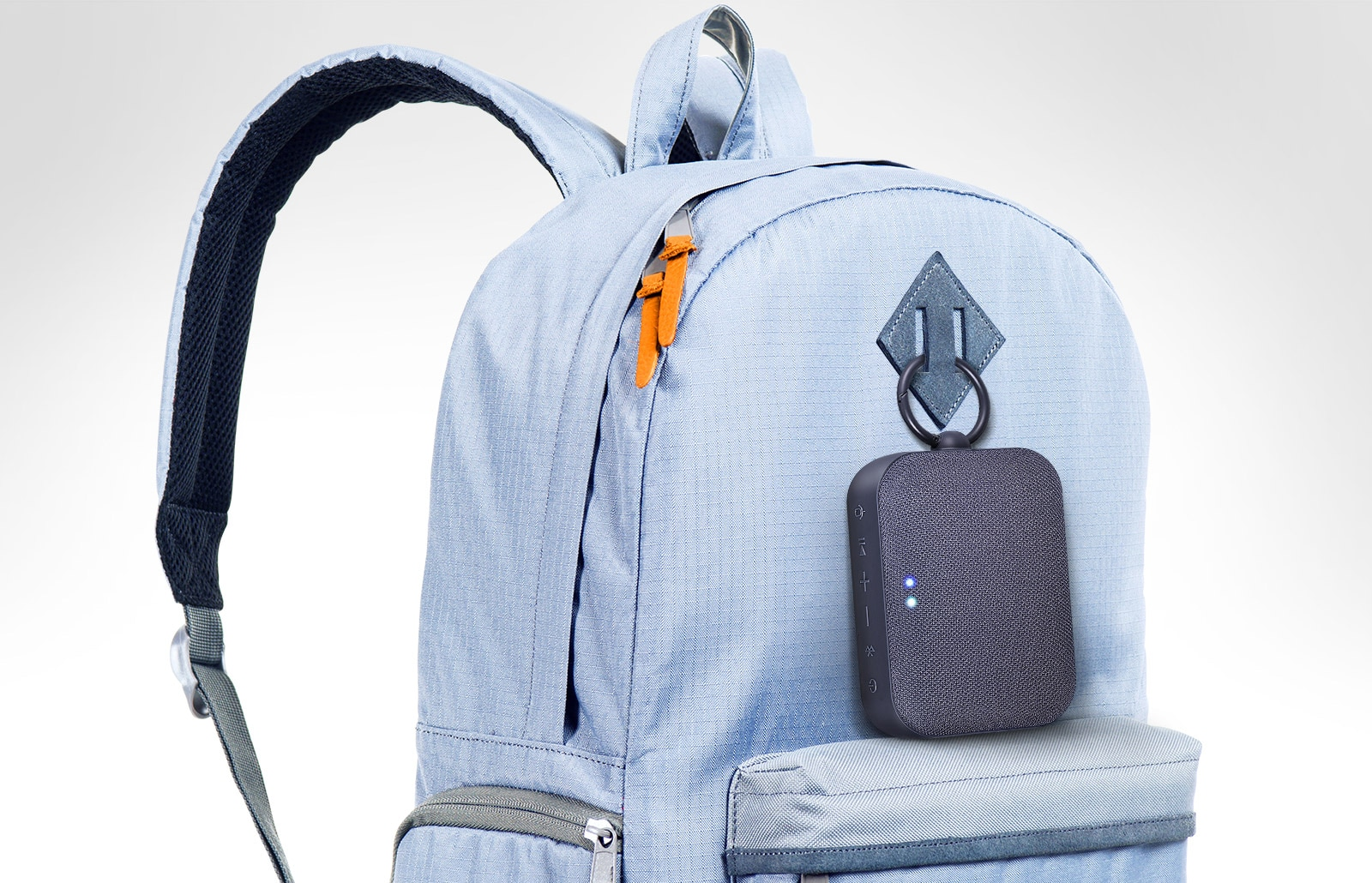 LG XBOOM Go PN1 is clipped onto the sky blue colored backpack.