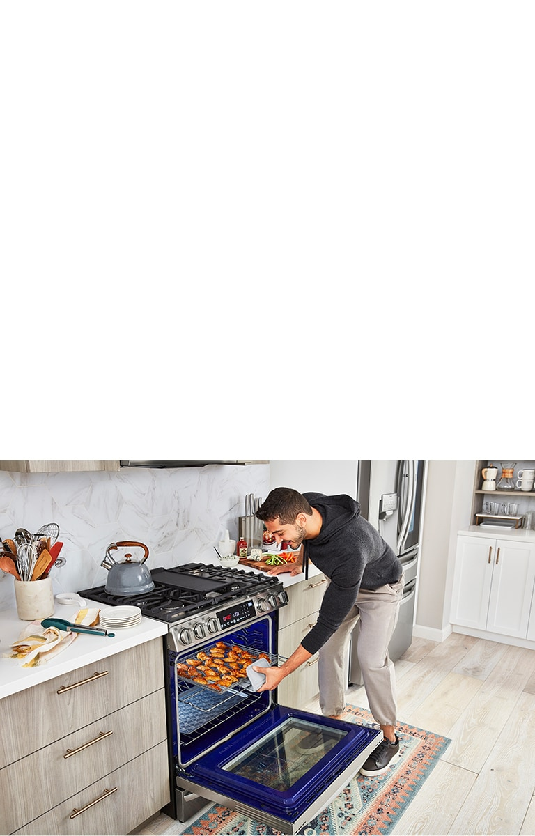 a man taking out air fried wings from the oven