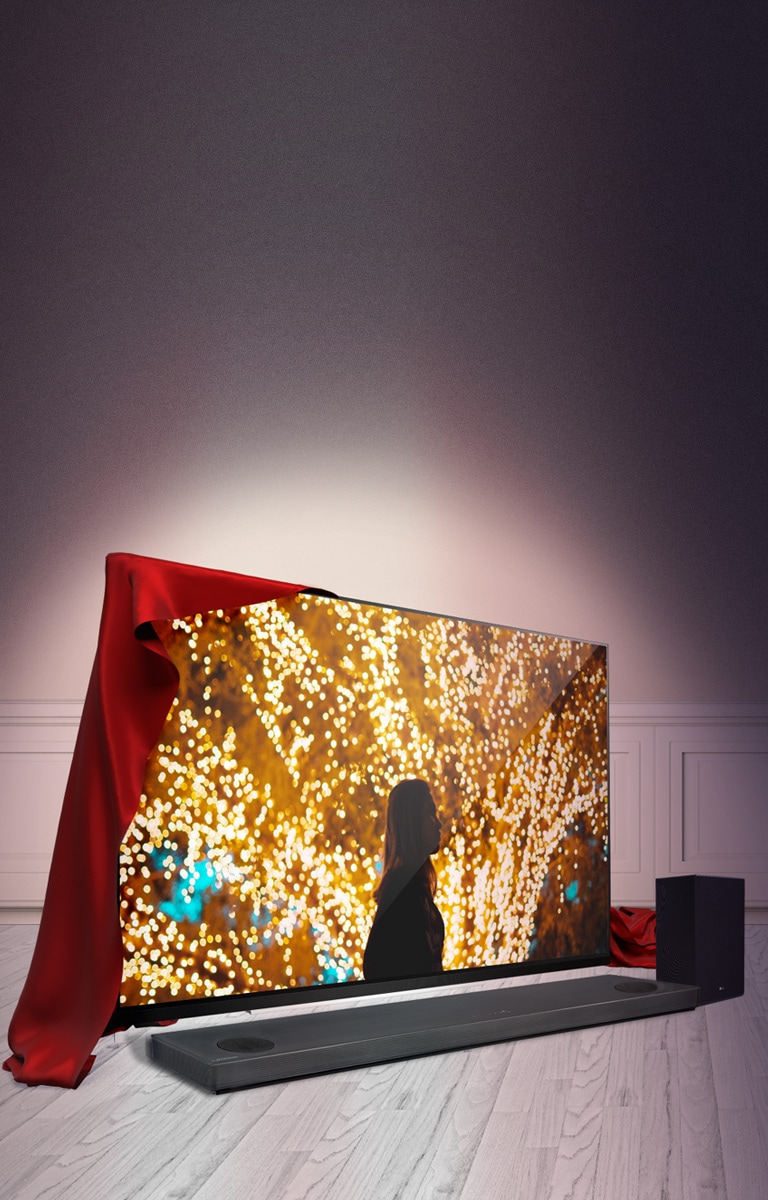Holiday Deals UHD TV on a wood floor with a red unveiling fabric on it.