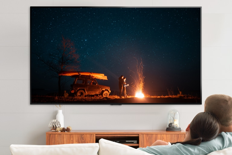 Homem e mulher assistindo tv no sofá