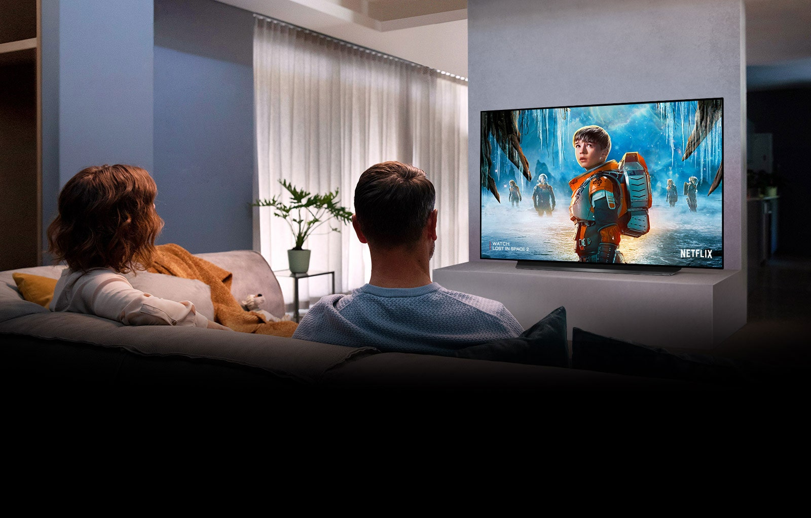 Couple sitting on a sofa in the living room watching a romantic movie on TV